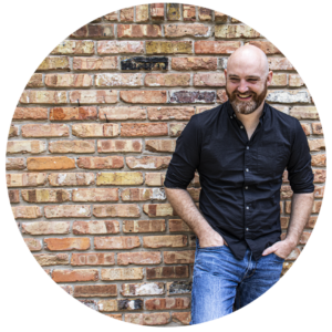 Dan Knight stands against a brick wall with his hands in his pockets.