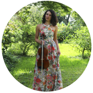 Nina Knight stands in a garden holding her viola.